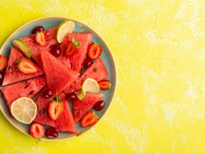 top-view-sliced-watermelon-with-sliced-lemons-strawberries-yellow-surface_140725-29891