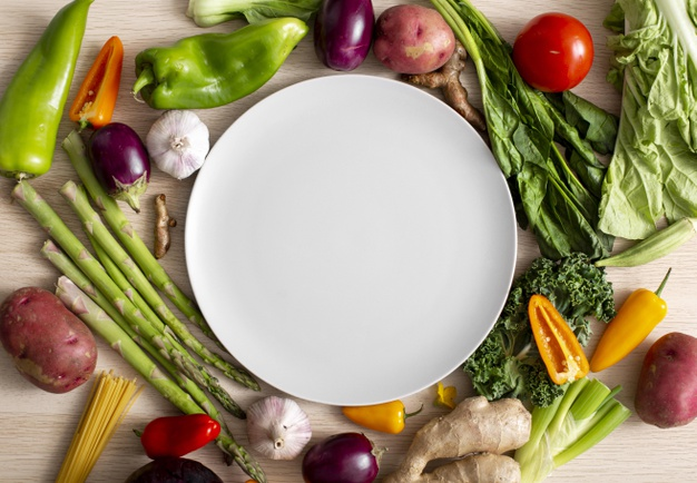 top-view-assortment-veggies-with-empty-plate_23-2148685439