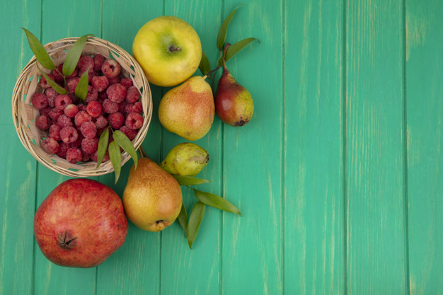 top view of raspberries in basket with pomegranate peach and apple on green background with copy space